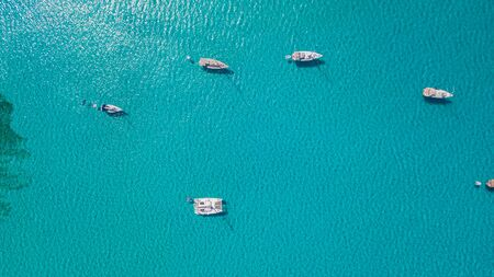 Amazing drone aerial landscape of the charming area of Es Trencs and the boats with a turquoise sea. It has earned the reputation of Caribbean beach of Mallorca. spain