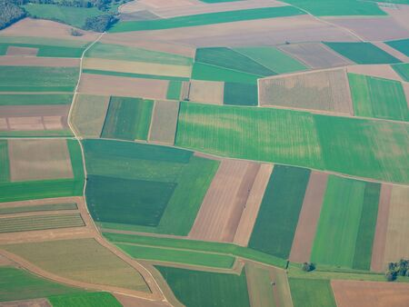 Earth's line. A vertical perspective of the ground's colors and shapes. Agricultural fields with green and brown colors. View from the airplane window Stok Fotoğraf - 132614328