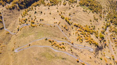 Road to the Gavia mountain pass in Italy. Up and down amazing aerial view creating beautiful shapes. Fall time. Warm colors. Nobody on the road
