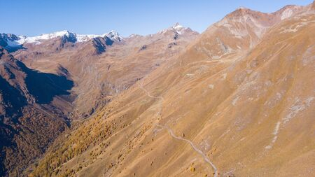 Road to the Gavia mountain pass in Italy. Amazing aerial view of the mountain creating beautiful shapes. Fall time. Warm colors. Nobody on the road