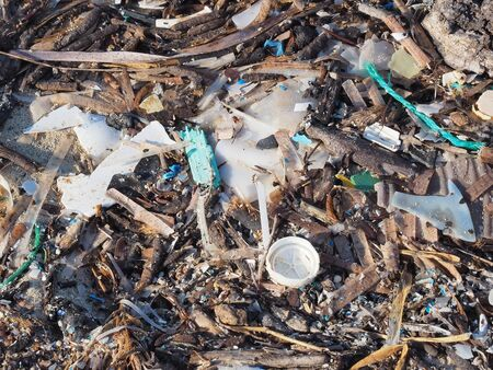 Environmental pollution. Sand beaches polluted with pieces of plastic waste. Micro plastics debris on the beach. Pieces of plastic residues Reklamní fotografie