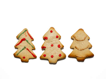 Homemade Christmas gingerbread cookies isolated on white background. Pine-shaped cookies. Decorated Christmas cookies