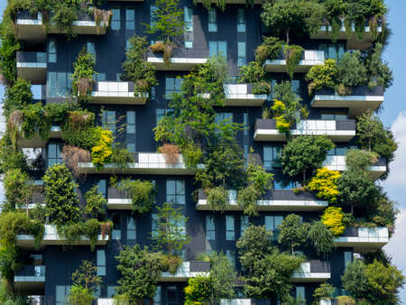 Milan, Italy. Bosco Verticale, a close up view at the modern and ecological skyscrapers with many trees on each balcony. Modern architecture, vertical gardens, terraces with plants