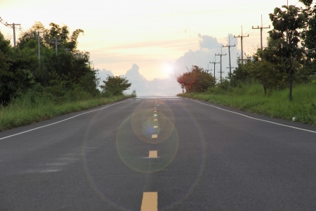 Paved country road with shiny sun Stock Photo
