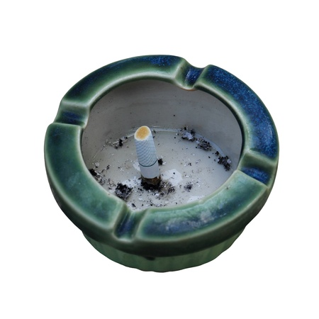Ceramic ashtray with cigarette on the stone table over white background