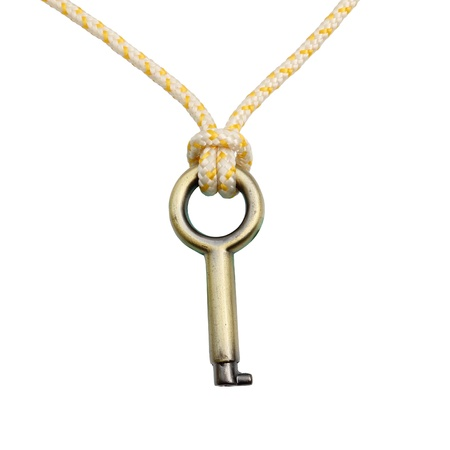 A Brass key hanging by a thread isolated over white background Stock Photo
