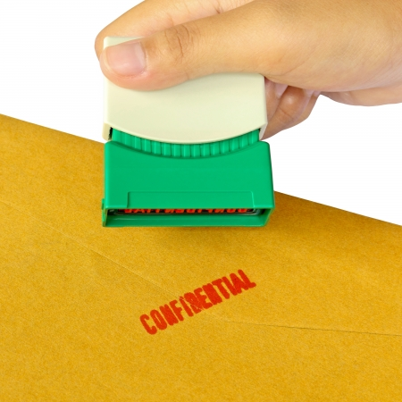 secrecy of voting: Holding a confidential stamper isolated over white background