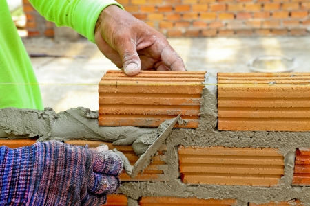 Worker create a brick wall with trowel and cement mortar
