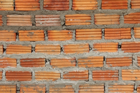 Red brick wall creating with cement mortar Stock Photo