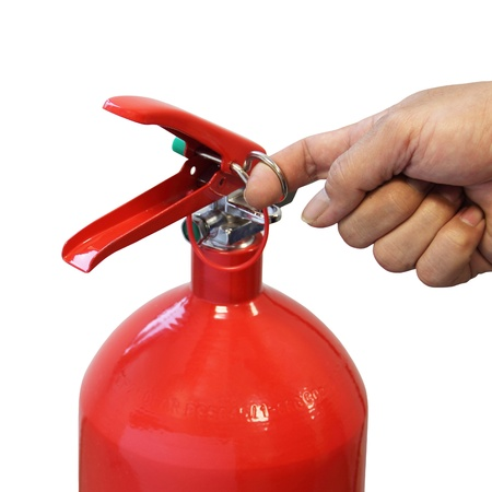 home safety: Hand pulling safety pin fire extinguisher isolated over white background