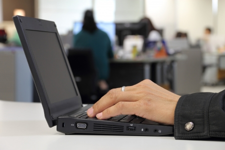 Employee hands working with laptop on the office background