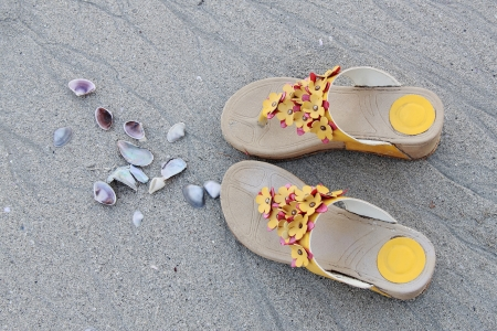 A design of shoes and seashell on the sand beach