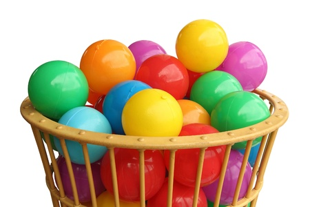Colour plastic balls in basket over white background