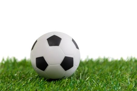 Soccer ball model on artificial green grass over white background Stock Photo
