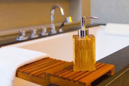 Liquid soap bottle on the bathtub in modern bathroom