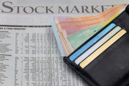 Money in a pocket over stock market newspaper background