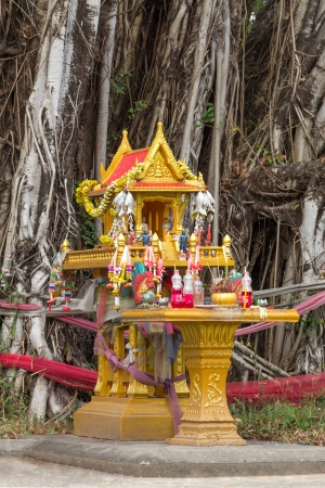 Yellow spirit house with flowers, food, incense, candle and jar under the big tree