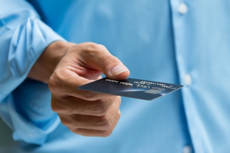 Closeup of hand holding and giving credit card for payment