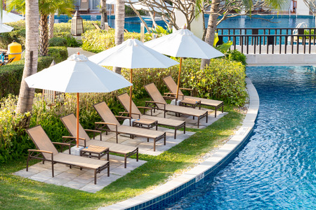 Relaxing chairs beside of swimming pool in residential garden Editorial
