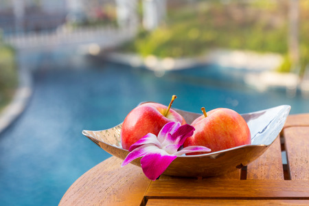 Bright apple with orchid in plate on the table over natual background.