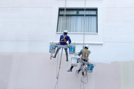 seguridad industrial: Dos trabajadores están pintando el color en edificios altos - Rise ocupación Foto de archivo