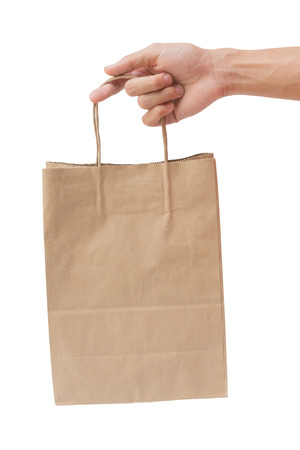 Hand holding and giving paper bag isolated over white background photo