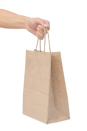 Hand holding and giving paper bag isolated over white background