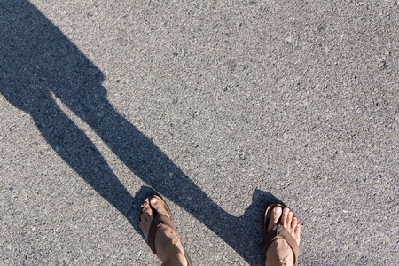 Shadow of someone wearing shoes standing on the road