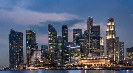 Singapore Business Tower at night, Cityscape and skyline panorama at dusk over the sea with colorful light.
