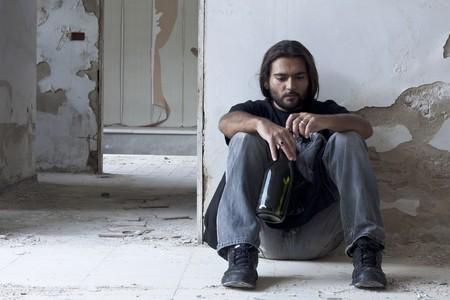 Alcoholische zittend op de vloer