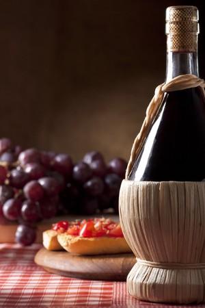 ブルスケッタとブドウとワインのフラスコ 写真素材