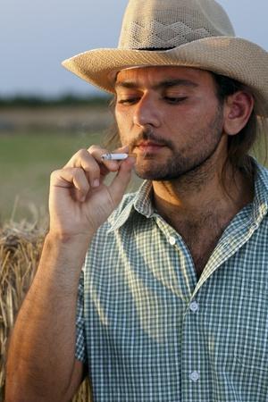 夕暮れ時、タバコを吸って干し草俵と農家 写真素材