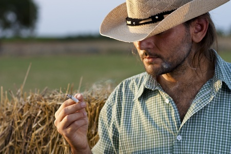 Cowboy with Hay Bale Smoking a Cigarette photo