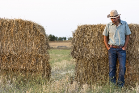 Farmer  at Sunset Standing with Hay Bales photo