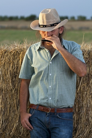 cowboy up: Cowboy with Hay Bale Playing Harmonica Stock Photo