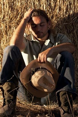 地面の上に座っての帽子を保持している疲れている農夫