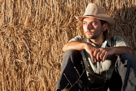 Cowboy with Hay Bale Sitting on the Ground photo
