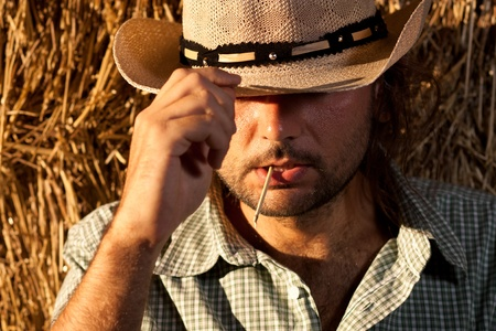 cowboy man: Cowboy with Straw in His Mouth Holding His Hat Stock Photo