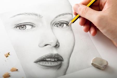 손을 연필로 여성의 얼굴을 그리기