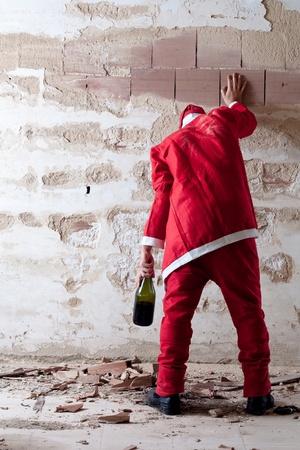 Duizelingwekkende Dronken kerstman Holding op een muur Stockfoto