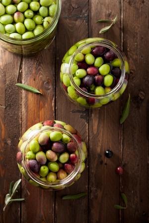 hoja de olivo: Aceitunas en salmuera (agua con sal en frascos de vidrio) en la madera Foto de archivo