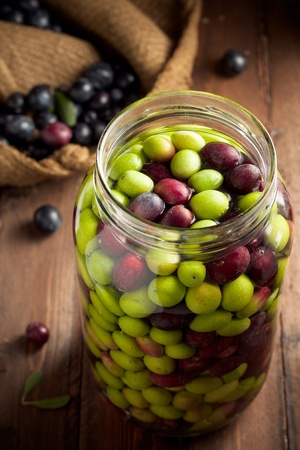 brine: Olives in Brine (with Water and Salt in Glass Jar) on Wood Stock Photo