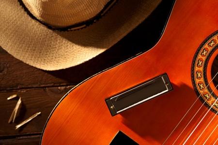 Harmonica op gitaar met cowboyhoed op hout Stockfoto