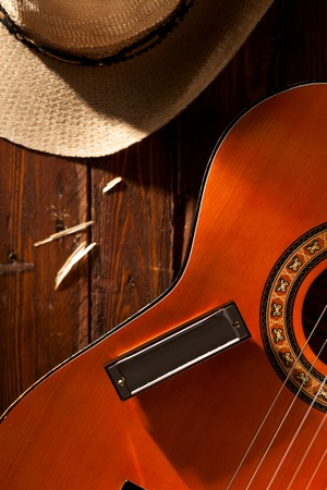 country life: Harmonica on Guitar with Cowboy Hat on Wood