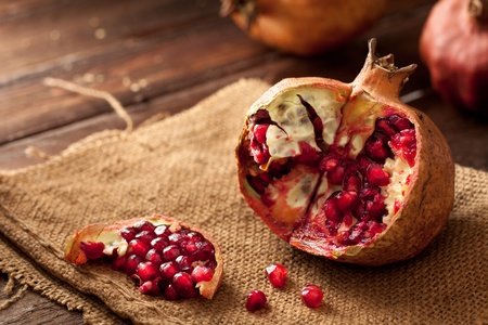 punica granatum: Pomegranate with Seeds on Jute and Wood Stock Photo