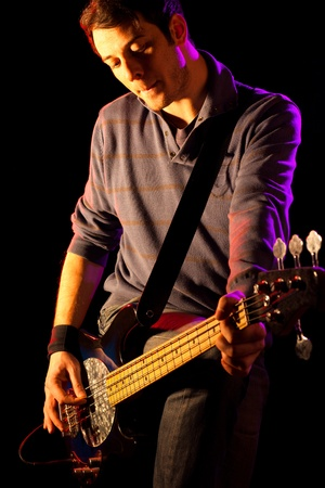bass player: Man Playing Electric Bass on Black Background