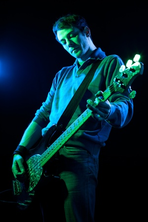 bassist: Man Playing Electric Bass on Black Background