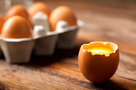Opened Egg Shell with Yolk on Wood Stock Photo - 12432310