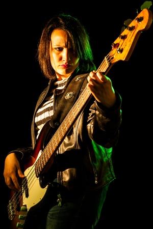 bassist: Rock Woman Playing Electric Bass Guitar