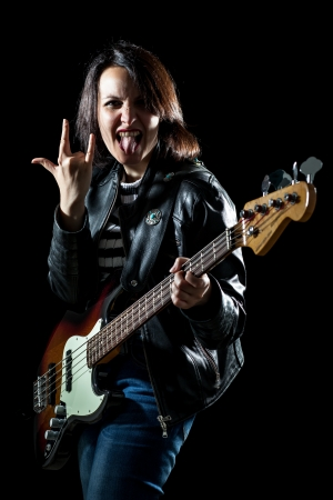 bassist: Rock Woman with Electric Bass Guitar Making the Sign of the Horns with Tongue Out Stock Photo